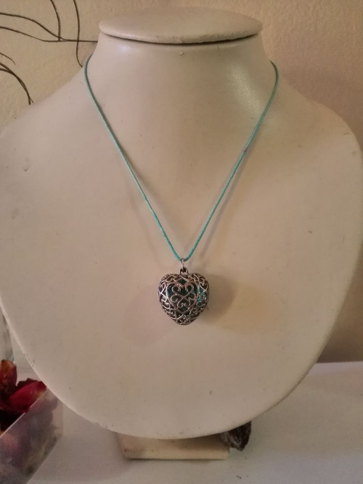A blue glass pebble in enclosed a heart pendant on ablue twine.