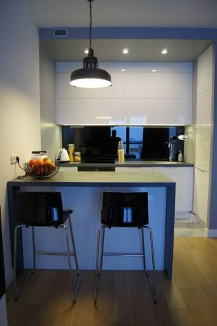 Fot. Kuchnia z frontami wykonanymi z białego akrylu (na ścianie czarne szkło Lacobel), Nataly Design,  www.nataly.pl