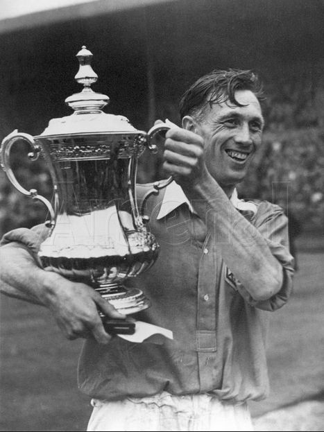 Arsenal captain Joe Mercer lifts the FA Cup in 1950. Joe made over (400) senior appearances and scored (4) goals. After retiring from playing Joe managed several teams such as Aston Villa, Coventry City, Sheffield Utd, and Manchester City. Joe was successful as a player winning many honors which followed him as a manager. In 2009 he was elected to the Football Hall of fame as a Manager