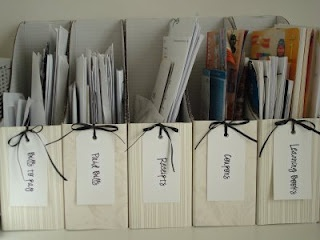 """ I bought a pack of 5 white cardboard magazine holders from Ikea for $2.99. I glued some scrapbook paper on the front of them with modge podge. Then I punched holes in the front and tied tags to each one with ribbon. I printed the labels from the computer. I have boxes for Bills to pay, Paid bills, Receipts, Coupons, and learning books."""
