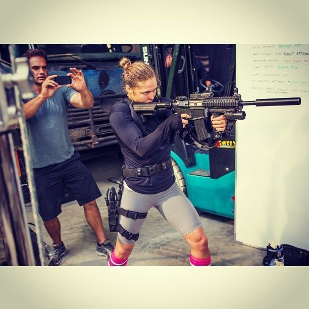 Ronda Rosey playing with a gun. It's about to get serious all up in here!!!!!