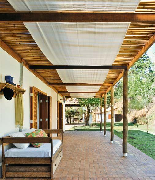 Pergolado com pilares de eucalipto, vigas comuns de madeira (6 x 6 cm e 6 x 12 cm) e taquaras de bambu. Por cima, telhas onduladas de plástico incolor.