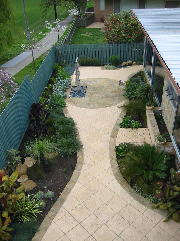 Hawthorn Residential Garden:  Two different paving materials form an hour glass shape, creating visual interest and drawing attention to the water feature.