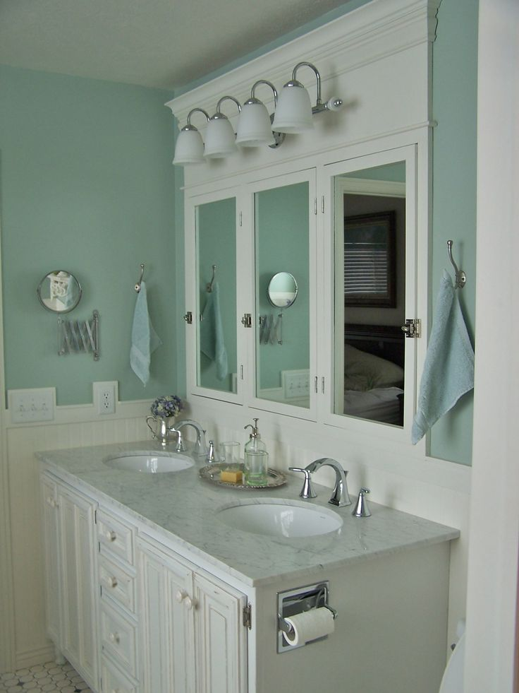 Farmhouse bathroom design - light aqua blue walls and white marble countertop. Lots of white! Love the mirror as a focal point.