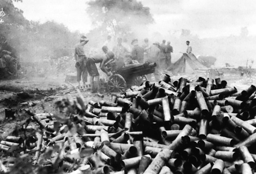 The spent 75-mm howitzer shells piling up outside the besieged Buremes city Myitkyina, mid-1944