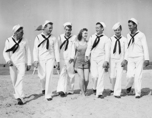 An unknown young woman with a group of sailors.  Date and photographer unknown.