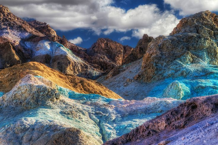 No need to adjust your screen, this technicolor terrain is Artist's Pallette at Death Valley National Park in California. Aprons of blue, pink, green, purple, brown and black drape across the mountain front. Metals and minerals affected by oxidation...