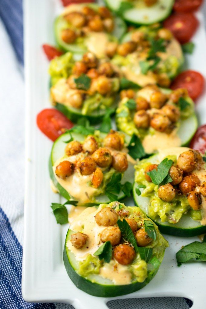 Cucumber appetizers lined up on a white plate with a blue and white napkin beneath it. Browned chickpeas and avocado top the cucumbers, with tomatoes in the background.
