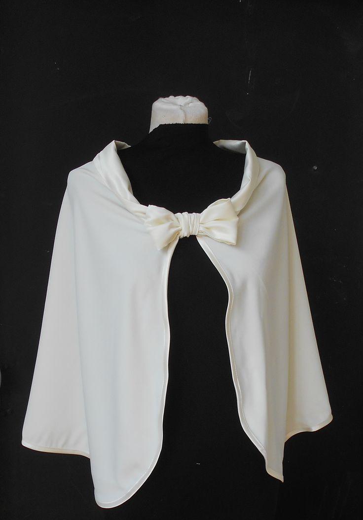 Jolie cape pour mariée de couleur ivoire avec un noeud élégant sur se devant. Élégante alternative au boléro pour porter au-dessus de la robe de mariée pendant un mariage d'hiver. D'une hauteur de 50 cm environ Faites en crépe ivoire , créme . Tissus doux , avec un beau tombant le tour de la cape est bordée d'un biais de satin ivoire. Le col est en satin duchesses assorti, orné d'un joli nœud  le dos présente un plis plat...