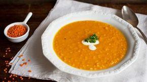 Ein Teller mit Linsen-Orangen-Suppe steht auf dem Tisch.