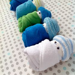 newborn diapers, a baby washcloth for the blanket, and a baby sock