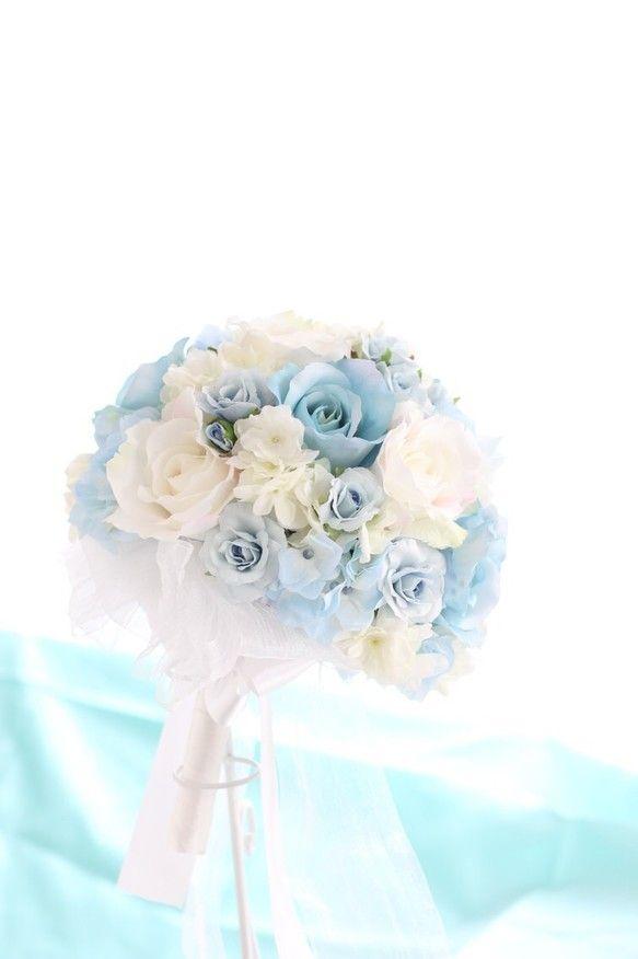 テーマカラーは水色♪美しい幸せ色のブーケです。テーマは、シンデレラウェディング♪素敵なウェディングシーンを最高のものにしてくれることまちがいなし!!主役のバラは、水色と花びらにピュアピンクが入った白、そして可愛らしい小さな水色のスプレーバラの3種類。バラのお花の間には、色と咲き方が異なる2種類の紫陽花を使っています。また、花嫁様の手元を美しく見せるように、ブーケの後ろ側には、ライトや光で光沢感が出るサテンとオーガンジーの2本のリボン。ドレスの色やラインを選ばずお持ちいただけるブーケです。きっとこのブーケで、大切なウェディングシーンがイメージ出来るのではないでしょうか。◎ ブーケとお揃いのヘアドレス、リストブーケのオーダーも承りますので、お問い合わせ下さい。☆ アーティフィシャルフラワー(最高級品質の造花)でお作りしています。◯サイズ:直径約20cm