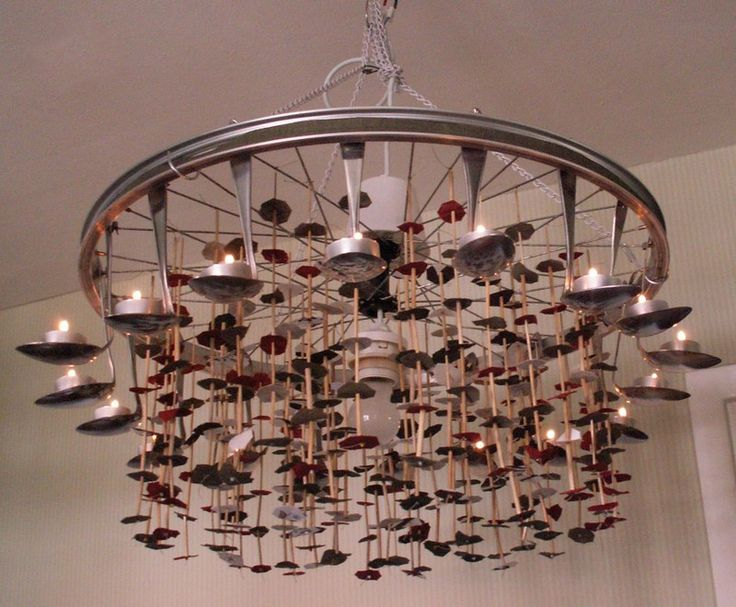 This is very nice spiky and shiny chandelier made from an old bicycle wheel and bent spoons.  -pinned for @Alvin Shavers