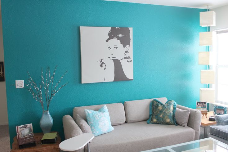 Interior living room design with grey fabric sofa and turquoise cushion also wall paint featuring picture wall as well as glass table and wood side table