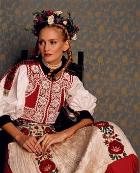 Hungary Bride Rhapsodies in bold embroidery, heart-stealing maidens inspired by Old-World folk customs wear layers of clothing topped with a beaded, paprika-colored velvet vest and a finely pleated silk apron. Rows of  braids, and a wildflower-and-heather wreath complement a visage as dewy as a mountain meadow.