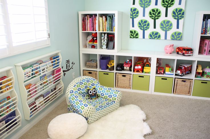 """In one corner of the room, a Land of Nod chair, Pier One pouf, and a hide rug found at Costco invite Adella and Nolan to curl up with a book. Ikea Expedit bookshelves make great storage for more toys and books. """"We leave the standard paperback and hardcover books up high where they can't be torn,"""" Lexi says. The DIY canvas tree print is actually a piece of stretched Ikea fabric.  Source: Adella & Co."""