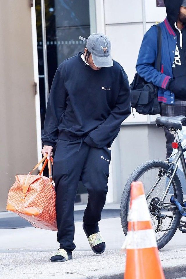 Travis Scott wearing Vetements Cut-Out Cuff Sweat Pants, Gucci Blooms Print Sandal, Goyard Duffle Bag, Vetements Reversible Double Crewneck Sweatshirt, Fan Merchandise Travis Scott Anti Tour Cap