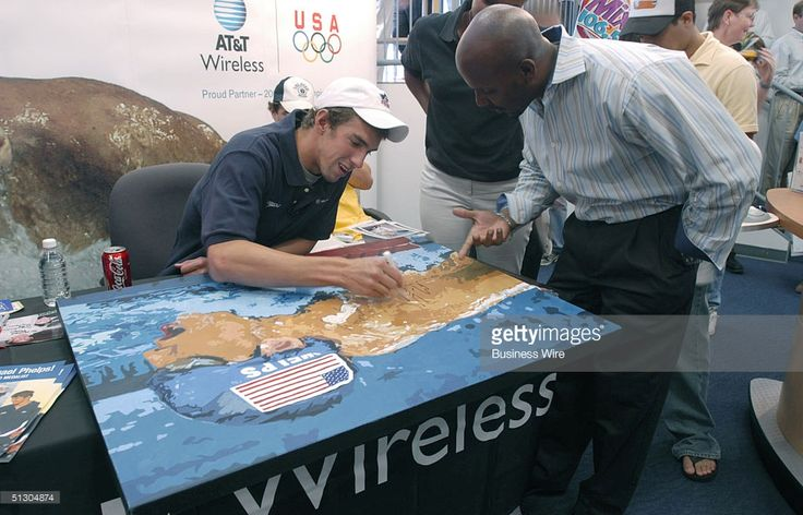 Olympic Gold Medalist Michael Phelps returns to his hometown outside of Baltimore. The Olympic athlete who came home from Athens with a record tying eight Olympic medals autographs a poster for a fan as he makes his first post games appearance for adoring fans at an AT&T Wireless store in Towson, Maryland.