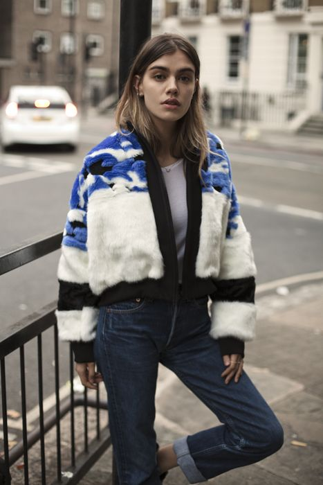 Blue, white, and black fur bomber jacket with cuffed dark wash jeans.