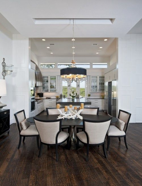 Refined chandelier and dining chairs, rustic wood floor and tree branch candle holder centerpiece, contemporary take on traditional wall wood treatment.