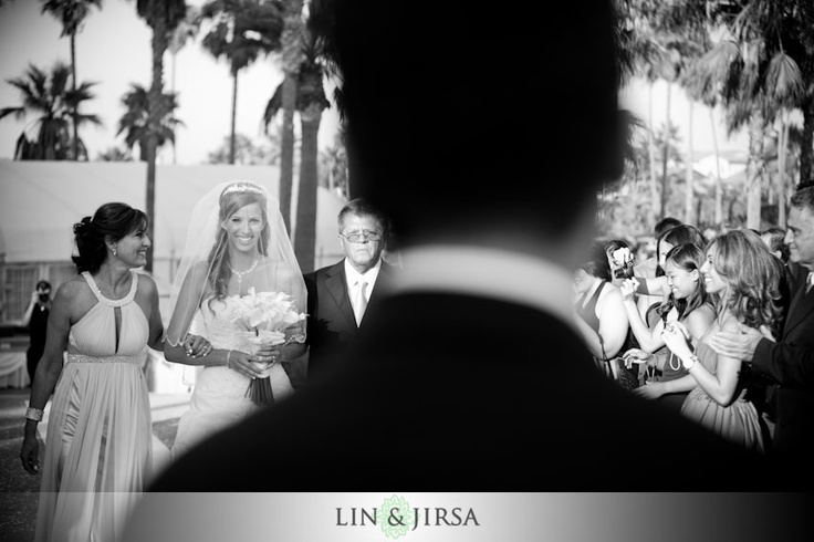 View of bride walking down the aisle from behind groom