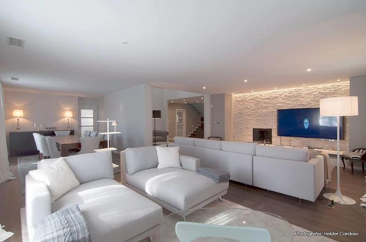 Un diseño en blanco muy íntimo. Cuando el color blanco domina toda la decoración, se siente muy bien, muy íntimo, con esos muebles cómodos en una habitación bien diseñada. Como único contraste, dentro de esa paleta neutra, es la pared de respaldo de la TV.