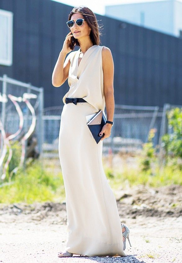 A neutral maxi dress is worn with a skinny bow belt, striped heels, and aviator sunglasses