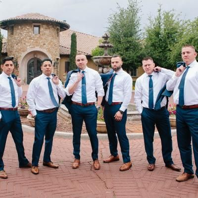 Handsome groom & groomsmen striking a pose together outside Villa Siena in white dress shirts & blue ties, complimented by brown shoes & navy pants  | Jasmine Amber Photography | villasiena.cc