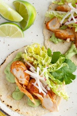 Spicy Fish Tacos - this healthier spin on a Mexican classic trades in battered fish and full-fat sour cream for pan-fried spicy fish filets and a flavourful avocado and yogurt sauce.
