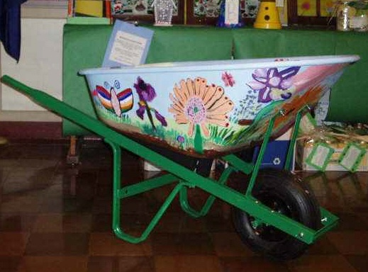 Wheelbarrow of Garden Wealth:    Fifth graders painted this wheelbarrow with a garden theme and filled it with everything you need for your garden. Materials and garden gear provided by classroom families