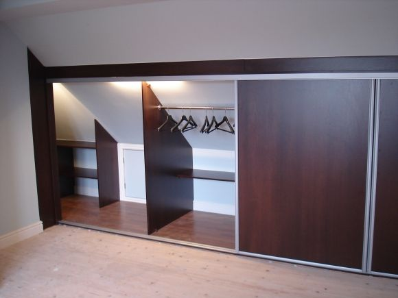 Create a luxury loft bedroom with angled ceiling wardrobes photo