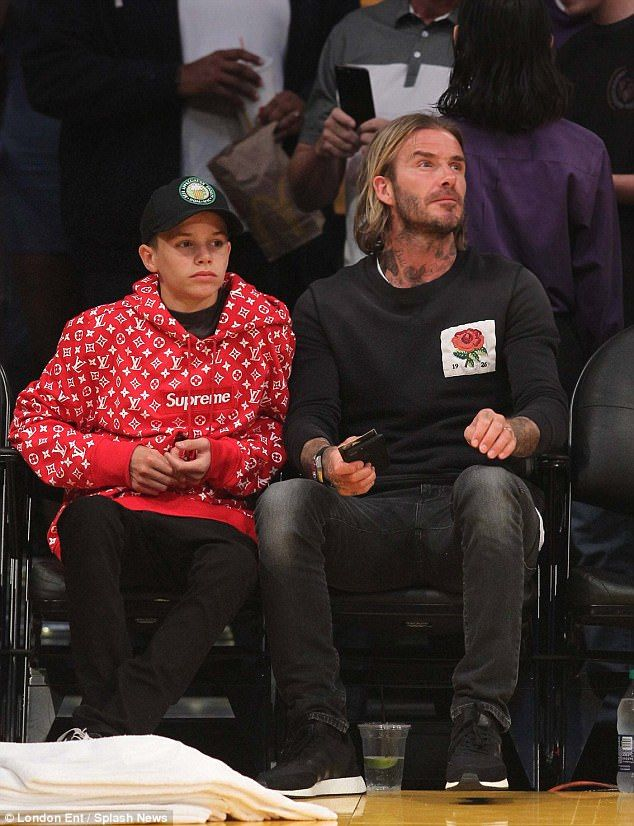 David Beckham with son Romeo  at the LA Lakers basketball game Oct. 2017. David wearing a Kent & Curwen Sweatshirt, Romeo wearing a red YSL Supreme X sweatshirt