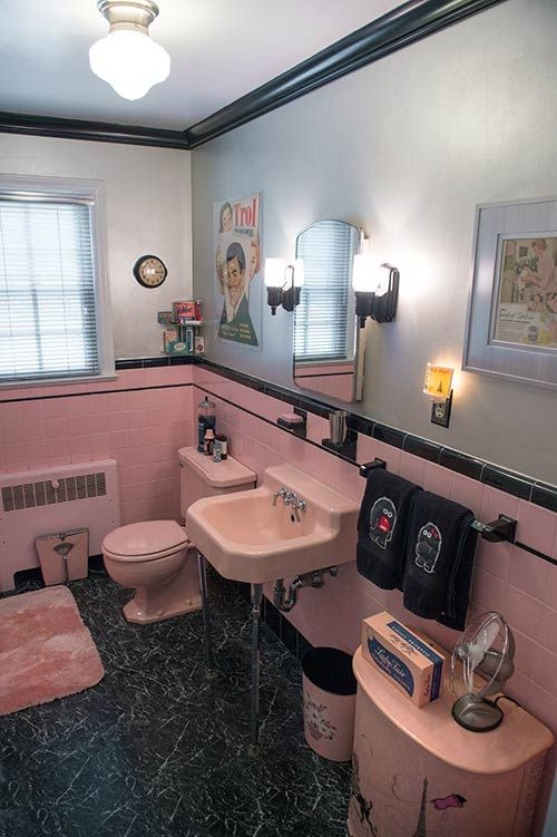 "Vintage pink & black bathroom.  Black ""marble"" vinyl.   Pink sink and toilet.  Black strip in middle of wall.  Black sconces.  Chrome walls."