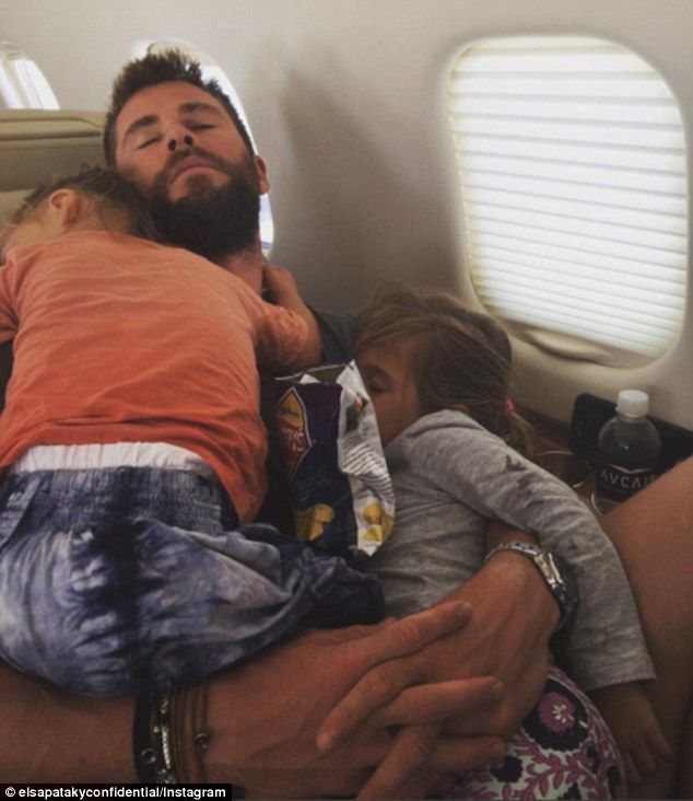 Family naptime: Chris Hemsworth was secretly snapped adorably cuddling his daughter India, four, and one of his two-year-old twin boys on a plane