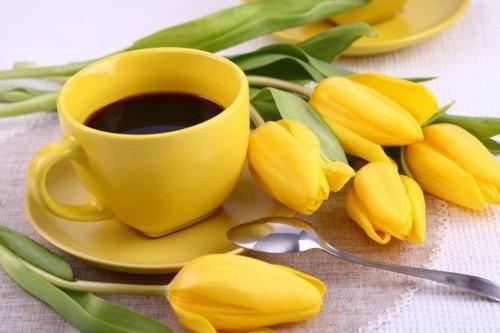 .yellow coffee mug and yellow flowers