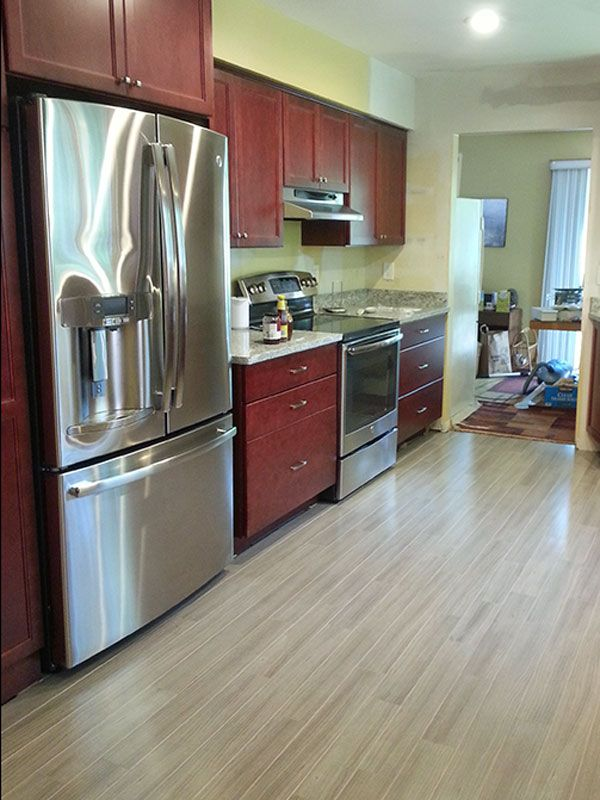 Grey hardwood floors accent a modern kitchen with cherry ...
