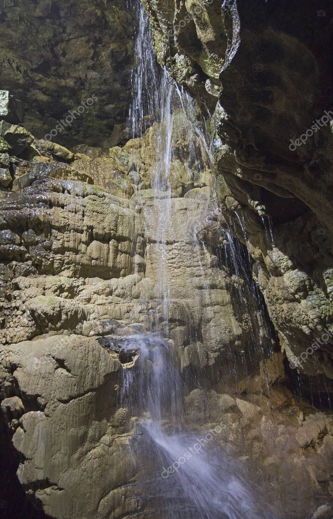 Geological rock formations and waterfall in an underground