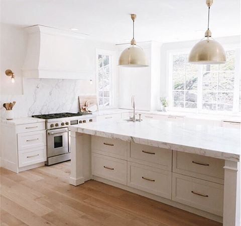 Drawers under marble waterfall counter in pretty white kitchen with brass accents!