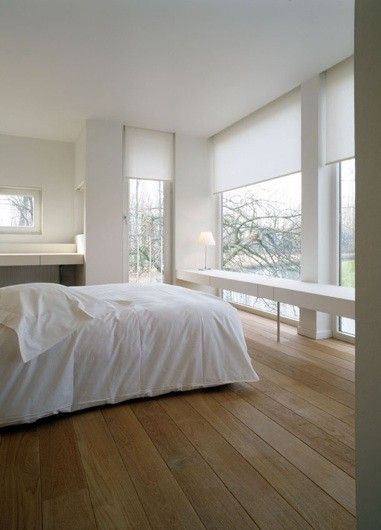 Modern white bedroom with a large expanse of glass and wood floors