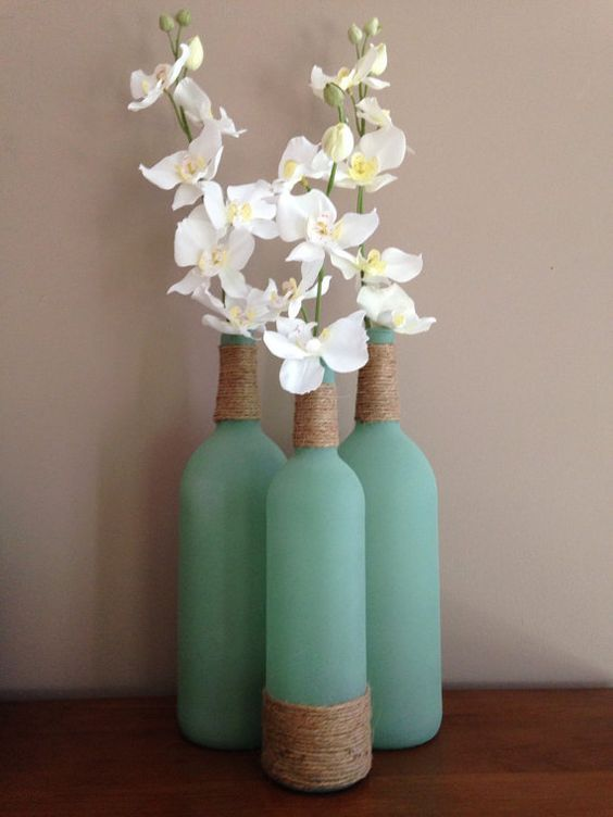 2 large & 1 regular size sea glass wine bottles wrapped with twine & filled with silk flowers. Perfect beachy home decor