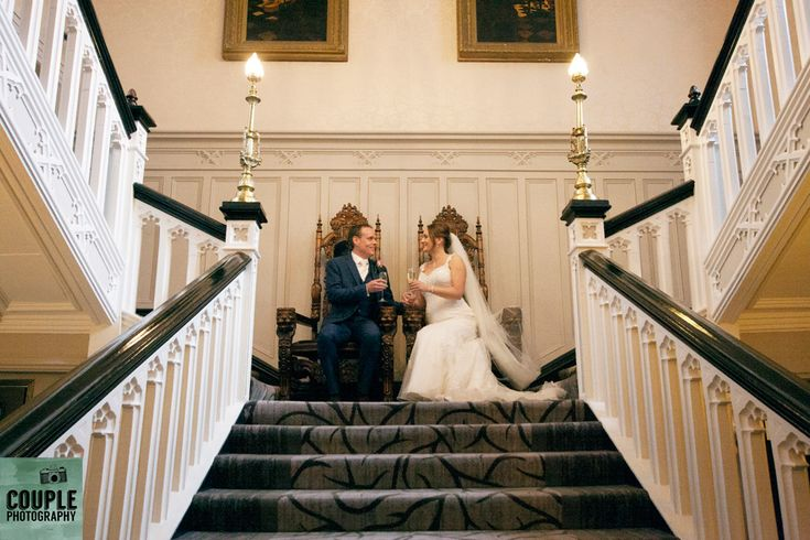 The newlyweds sit on top of the famous staircase. Weddings at Clontarf Castle Hotel by Couple Photography.