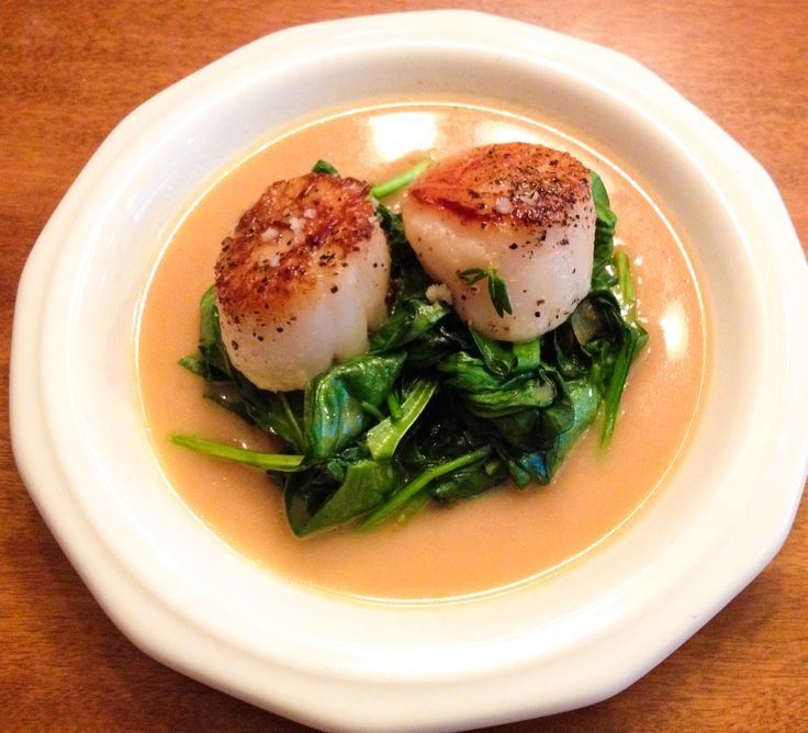 Seared scallops with orange brandy cream sauce over sautéed spinach