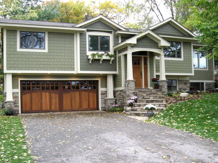 This lovely split-level home blends in beautifully with the trees and lawn around it, thanks to its soft gray-green siding. The stone facade and steps provide a touch of nature while the carriage-style garage doors and elegant wood front door add a bit of Craftsman charm.