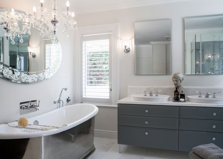 The pewter free standing bath with the custom designed mirror and satin glass back painted vanity adds sophisticated glamour.