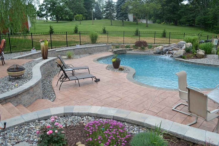 Beautifully designed backyard space features textured steps and large Ashler slate stamped pool deck and patio.  Dantam Stamped Concrete Works Dillsburg, PA