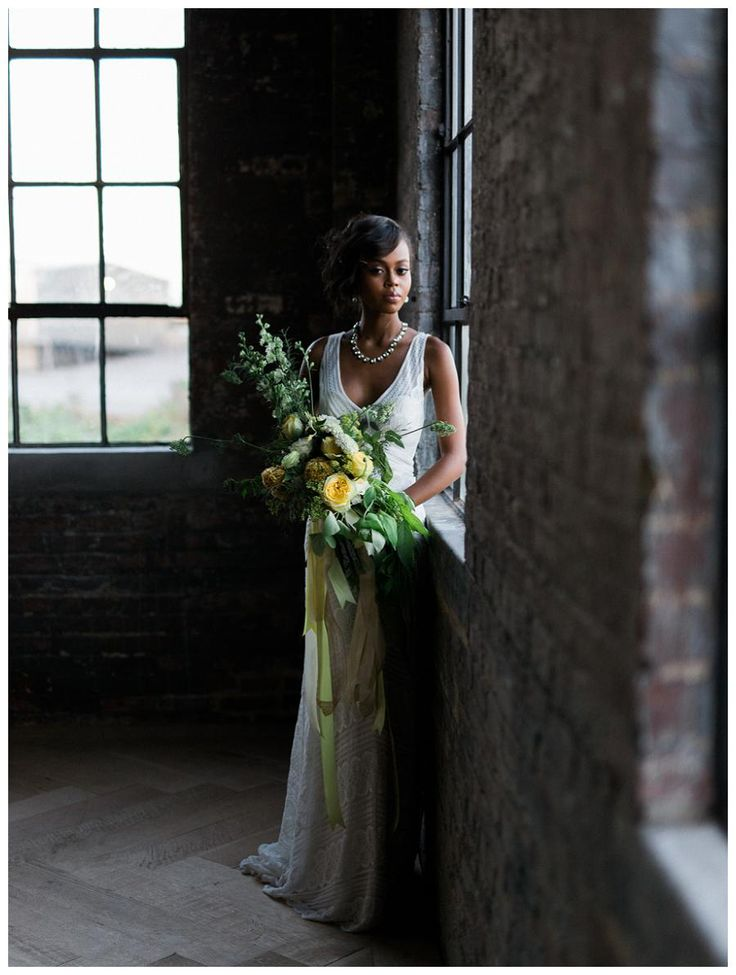 Beautiful bride with a bouquet of yellow and ivory blooms. Dress by Wtoo from The White Magnolia Bridal Collection in Atlanta, GA, accessories from Perfect Details. Bouquet by Amanda Jewel Floral + Design. Model styling by Chawncia Bythwood, hair and makeup by Scoobie West & Company. Photographed at Bishop Station in Atlanta, GA by Elle Golden Photography.