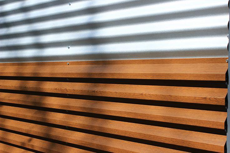 Gard metalic mixt din panouri alb-imitatie de lemn natur.