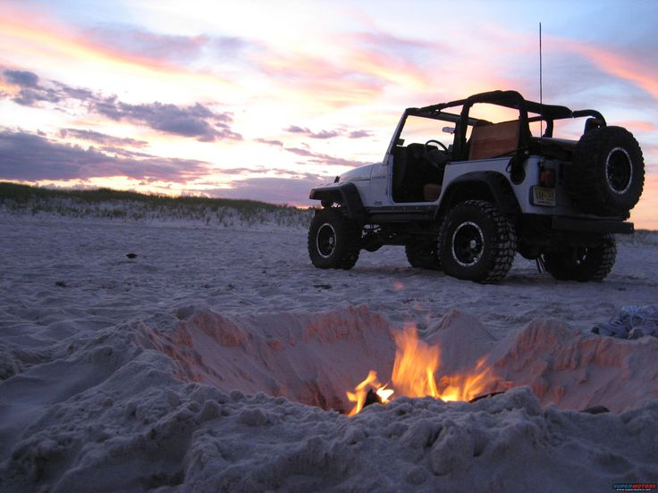 Amazing shot of a modified Jeep TJ by a fire on the beach