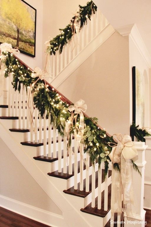 natural garland, white lights, gold bows draped on handrail of staircase. beautiful christmas decor.