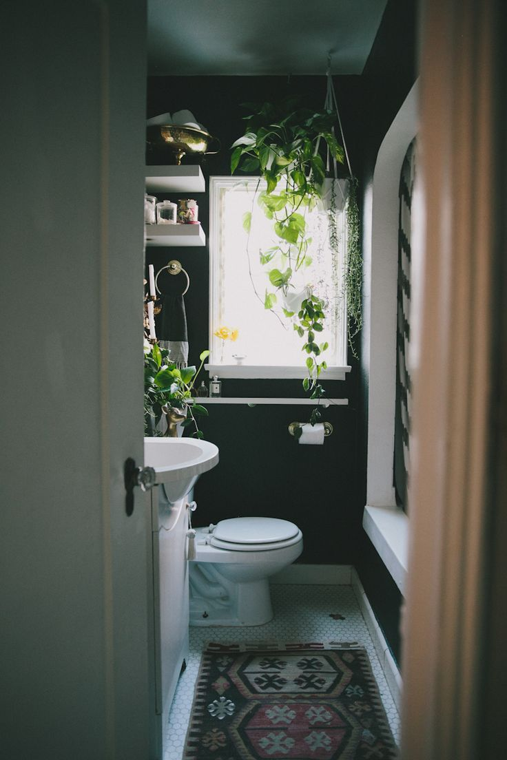 Dark walls with white accents in a tiny bathroom.  Paint is Martha Stewart in Francesca Black.